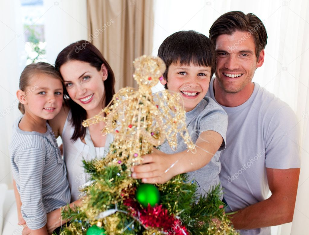 Portrait of a family decorating a Christmas tree in the living-room  Stock Photo #10295546