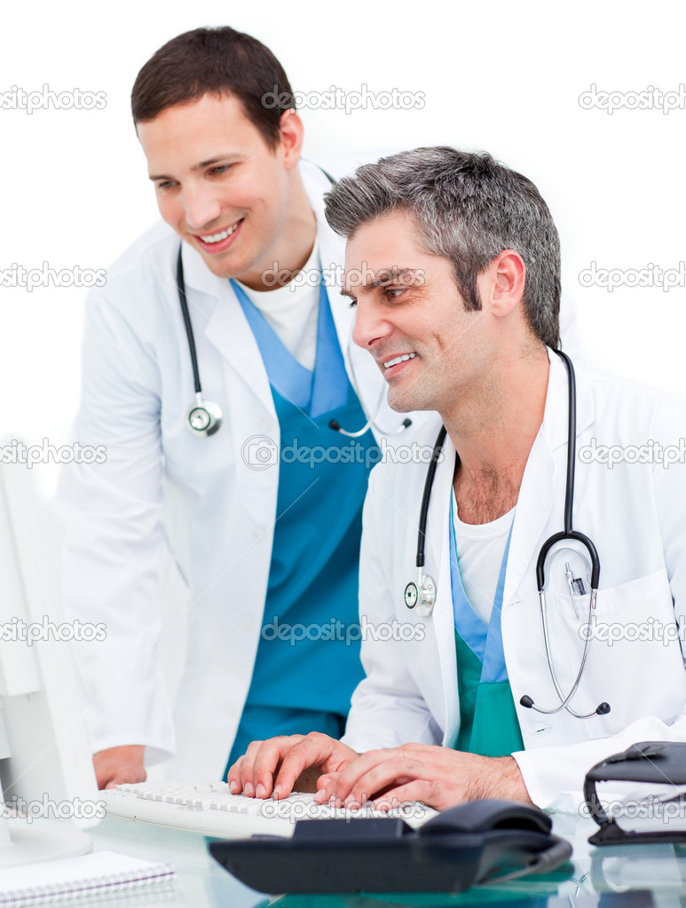Two male doctors working at a computer against a white background  Stock Photo #10295663