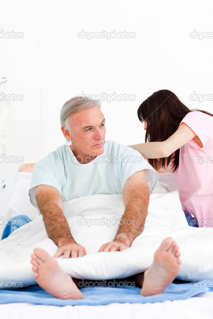 Female nurse adjusting pillows for a senior patient in a hospital — Stock Photo #10296029