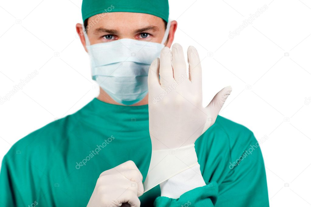 Charismatic surgeon wearing surgical gloves against a white background  Stock Photo #10296655