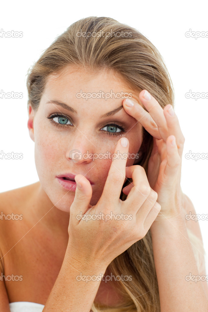 Concentrated woman putting a contact lens isolated on a white background — Stock Photo #10297475