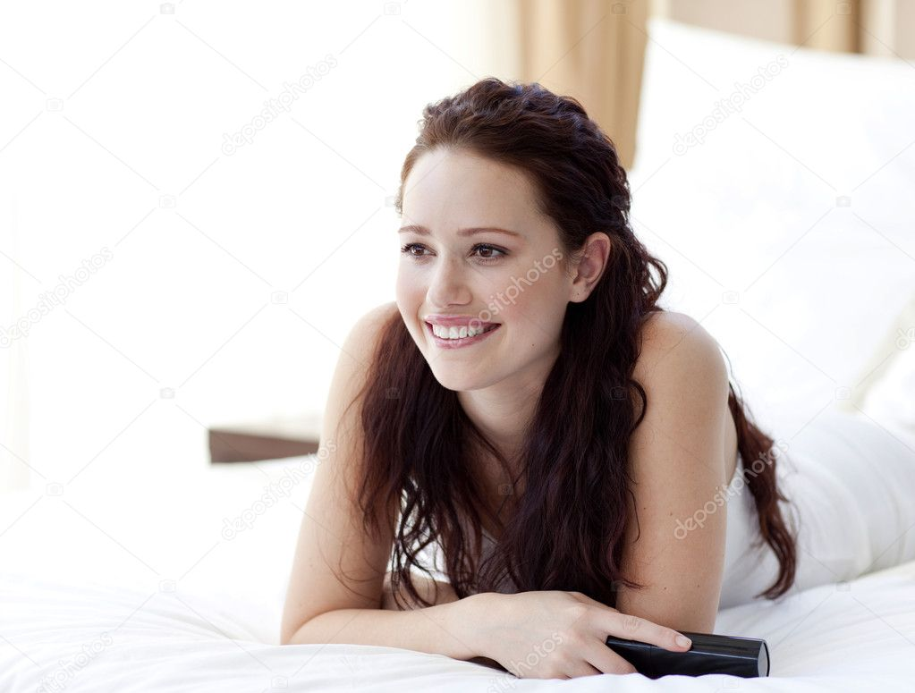 Smiling beautiful woman watching television in bedroom — Stock Photo #10297848