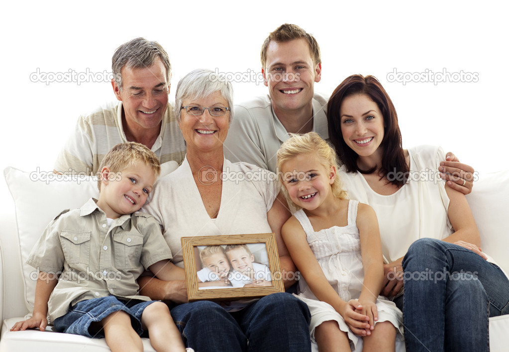 Family holding a portrait of children sitting on sofa at home  Stock Photo #10297989