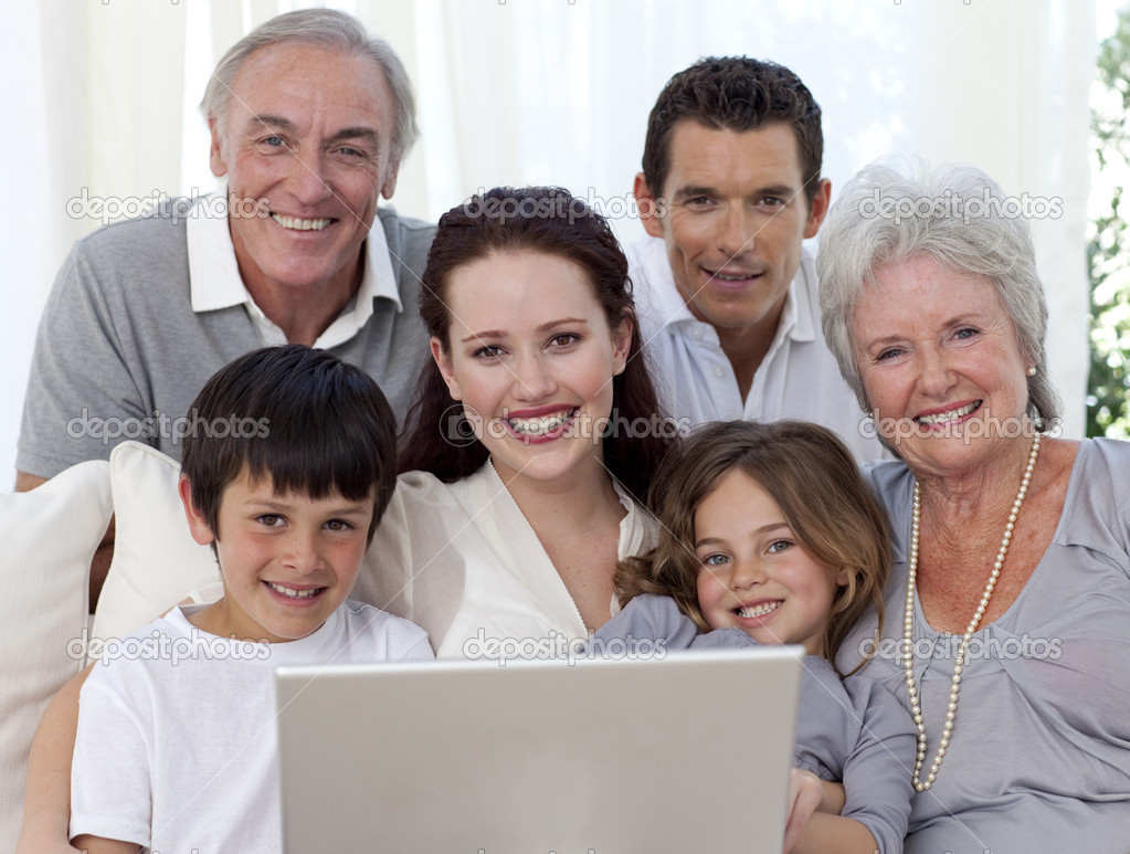 Portrait of smiling family sitting on sofa using a laptop — Stock Photo #10298031