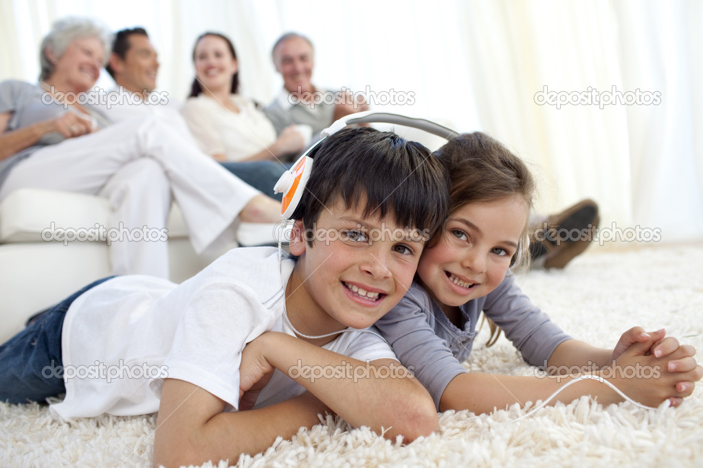 Children on floor listening to the music in living-room with their family on sofa  Stock Photo #10298072