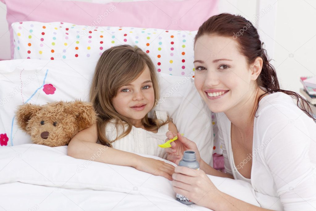 Sick little girl in bed taking cough medicine with her mother  Stock Photo #10298509