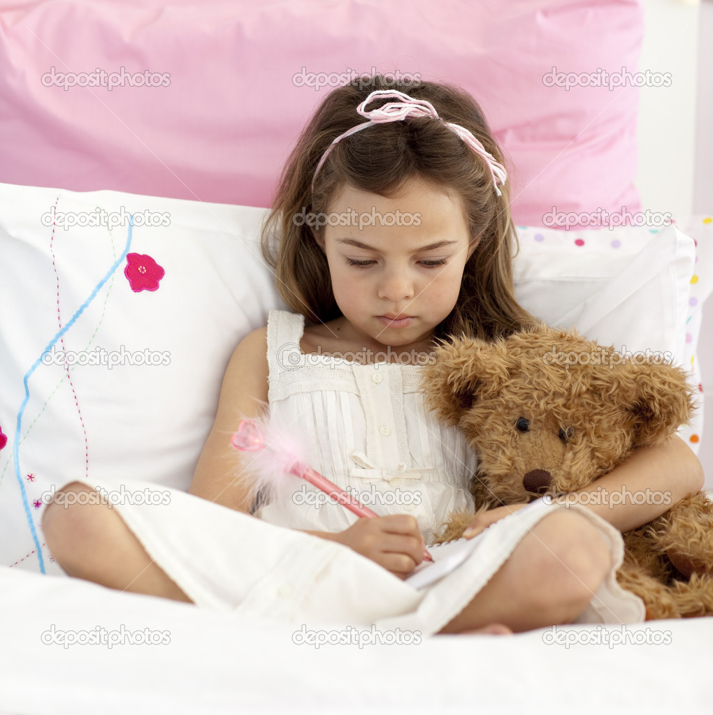 Little girl sitting in bed writing in a notebook — Stock Photo #10298570