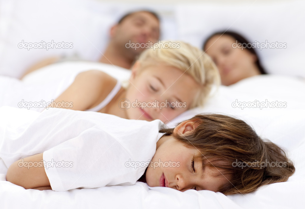 Children sleeping with his parents in a big bed — Stock Photo #10299018