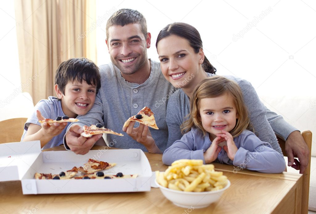 padres e hijos a comer pizza y papas fritas en casa foto stock wavebreakmedia 10299063. Black Bedroom Furniture Sets. Home Design Ideas