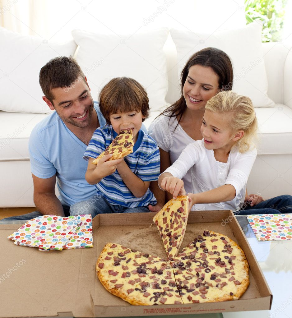 Young family eating pizza in living room stock photo for Living room ideas young family