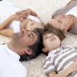 Stock Photo: Family lying on floor at home with heads together