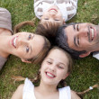Happy family lying in a park — Stock Photo