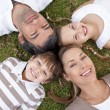 Smiling family lying in a park — Stock Photo