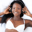 Bright woman in underwear listening music — Stock Photo