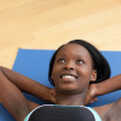 Smiling woman in gym clothes doing sit-ups — Stock Photo