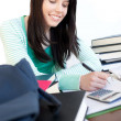 Royalty-Free Stock Photo: Cheerful teen girl studying on a desk