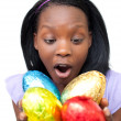 Joyful woman holding colorful Easter eggs - Stock Photo