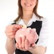 Woman putting money in a Piggy Bank — Stock Photo