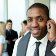 Ethnic businessman on phone in office — Stock Photo