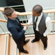 Two businessmen shaking hands on stairs — Stock Photo