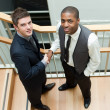 Two businessmen shaking hands on stairs and smiling at the camera - Stock Photo