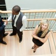 High view of two businessmen shaking hands and a businesswoman with folded arms — Stock Photo
