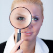 Serious Business woman looking through a magnifying Glass — Stock Photo #10301355