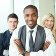 Afro-American businessman with his colleagues smiling at the cam — Stock Photo