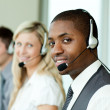 Businesspeople with headsets smiling at the camera — Stock Photo