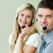 Two business smiling at the camera with headsets — Stock Photo #10301603