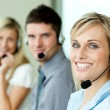 Young businesspeople smiling at the camera with headsets — Stock Photo #10301614