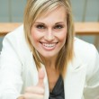 Businesswoman smiling with her thumb up — Stock Photo #10301640