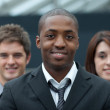 Afro-American businessman smiling at the camera with his team — Stock Photo