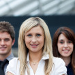 Smiling blonde businesswoman leading her team - Stock Photo
