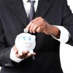 primer plano de un empresario poner dinero en su alcancía — Foto de Stock