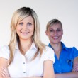 Businesswoman smiling at the camera with her colleague — Stock Photo