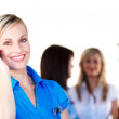 Businesswoman on phone with her team in the background — Stock Photo