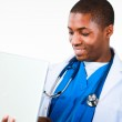 Close-up of an friendly Afro-American doctor working on a laptop — Stock Photo