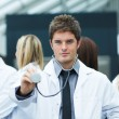 Handsome young doctor in front of his team — Stock Photo #10302276