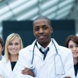 Afro-American doctor leading his team with folded arms - Stock Photo
