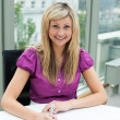 Portrait of a blonde businesswoman smiling at the camera — Stock Photo