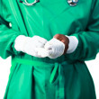Foto Stock: Surgeon putting on his gloves