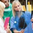 Beautiful female doctor shwoing X-ray to her colleagues — Stock Photo