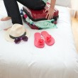 Close-up of a woman trying to close her suitcase — Stock Photo