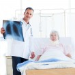 A doctor showing an x-ray to a patient — Stock Photo