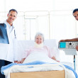 Senior patient looking at an x-ray with her doctor — Stock Photo