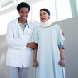 Smiling doctor helping a female patient on crutches — Stock Photo