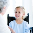 Blond little girl sitting on a wheelchair talking with her grand — Stock Photo #10304348