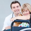 Stock Photo: Cute little girl sitting on wheelchair with her doctor
