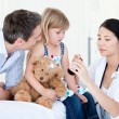 Confident asian female doctor giving syrup to a little girl — Stock Photo